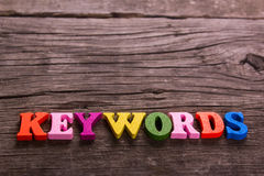 Keywords word made of wooden letters. Keywords word made from colored wooden letters on an old table. Concept Stock Photo