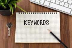 Keywords concept with computer keyboard and pencil. Keywords word on notebook with computer keyboard and pencil on wooden table Royalty Free Stock Photo