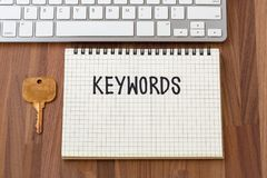 Keywords word on notebook with key. On wooden table Royalty Free Stock Images