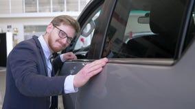 Kfz-Werkstatt, junger Kundenmann in Brillen mit der Freude, die neues Automobil leicht lächelnd an der Verkaufsstelle streicht stock footage