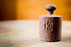 1 kg rusty weight in shallow focus. Old rusty measurement steel piece royalty free stock image