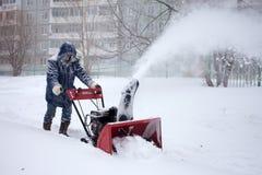 KHABAROVSK, RÚSSIA - 3 DE DEZEMBRO DE 2015: Um homem que remove a neve com Imagens de Stock Royalty Free