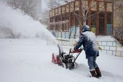 KHABAROVSK, RUSLAND - DECEMBER 03, 2015: Een mens die sneeuw verwijderen met Stock Afbeeldingen