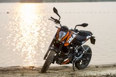 Khabarovsk Ryssland - Juli 27, 2014: hertigen för motorcykeln KTM står på kusten av en sjö i Khabarovsk på Juli 27, 2014 Arkivfoto
