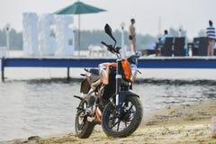 Khabarovsk Ryssland - Juli 27, 2014: hertigen för motorcykeln KTM står på kusten av en sjö i Khabarovsk på Juli 27, 2014 Royaltyfria Foton