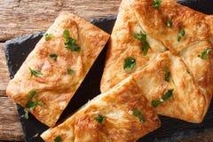 Khachapuri是乳酪充满的面包一个传统英王乔治一世至三世时期盘  装填包含乳酪sulguni,蛋水平的顶视图 免版税库存图片
