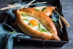 Khachapuri -英王乔治一世至三世时期乳酪和鸡蛋被填装的面包 免版税库存图片
