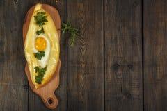 Khachapuri avec la cuisine caucasienne de légumes frais, plan rapproché sur une table en bois noire Khachapuri adjarien Vue de ci Photo stock