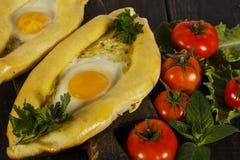 Khachapuri avec la cuisine caucasienne de légumes frais, plan rapproché sur une table en bois noire Khachapuri adjarien Vue de ci Images stock