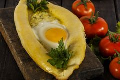 Khachapuri avec la cuisine caucasienne de légumes frais, plan rapproché sur une table en bois noire Khachapuri adjarien Vue de ci Images libres de droits