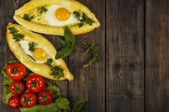 Khachapuri avec la cuisine caucasienne de légumes frais, plan rapproché sur une table en bois noire Khachapuri adjarien Vue de ci Image stock