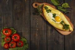 Khachapuri avec la cuisine caucasienne de légumes frais, plan rapproché sur une table en bois noire Khachapuri adjarien Vue de ci Photographie stock