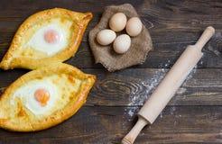 Khachapuri com os ovos no pano de saco, farinha, ovos imagem de stock