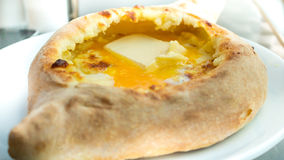 Khachapuri di Adjaruli, riempito di formaggio e completato con un crudo per esempio fotografia stock