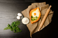 Khachapuri with eggs on sackcloth, flour, eggs and parsley on black table, space for text Stock Image