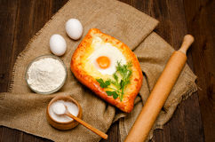 Khachapuri with eggs on sackcloth, salt, flour and eggs on the wooden table Royalty Free Stock Images