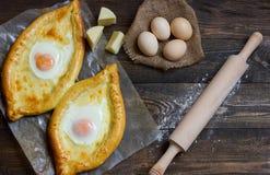 Khachapuri na mące, jajkach i tocznej szpilce na czerń stole, odgórny widok Zdjęcia Royalty Free