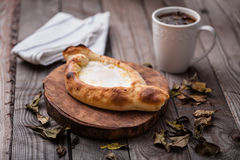 Khachapuri Pastry and Mug of Tea. Traditional Georgian cheese khachapuri flatbread pastry with mug of tea on a wooden table with fall tea leaves Royalty Free Stock Photography