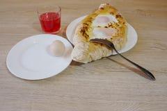 Khachapuri, raditional georgische Käse-gefüllte Brot Ajarian-Art khachapuri mit Eiern auf dem Tisch Stockbild
