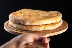 Khachapuri tradicional georgiano de la comida en el plato de madera en fondo negro imágenes de archivo libres de regalías