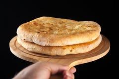Khachapuri tradicional georgiano de la comida en el plato de madera en fondo negro imagen de archivo libre de regalías