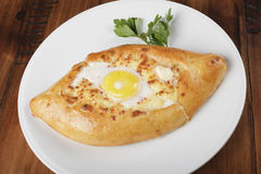 Khachapuri - traditional georgian pie. With potatoes and cheese. Cake on a white plate. Wooden background Stock Images
