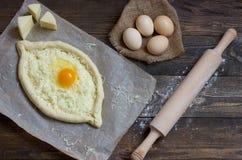 Khachapuri z mąką, jajkami i toczną szpilką na czerń stole, Gruzińska kuchnia Zdjęcia Stock
