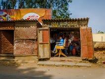KHAJURAHO INDIEN - DEC 21, 2014: Oidentifierat folk i en yrkesmässig frisör i gatasalong Khajuraho är liten Arkivfoton