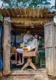 KHAJURAHO INDIEN - DEC 21, 2014: Oidentifierat folk i en yrkesmässig frisör i gatasalong Khajuraho är liten Royaltyfri Foto