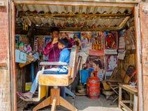 KHAJURAHO INDIEN - DEC 21, 2014: Oidentifierat folk i en yrkesmässig frisör i gatasalong Khajuraho är liten Royaltyfria Bilder