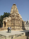 Khajuraho. My friend listens to Hindu man in front of one of  Khajuraho temples Stock Photo