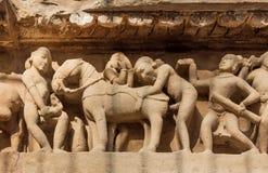 Интимная жизнь древние люди на каменном сбросе на стене виска Khajuraho, Индия Место наследия Unesco Стоковые Изображения