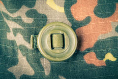 Khaki button on the fabric with a camouflage pattern. Background Stock Photos