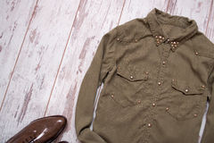 Khaki-colored shirt with rivets, lacquered shoes. Wooden background, space for text. Fashion concept. Stock Image