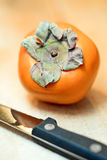 Khaki fruit with knife to cut it in slices Stock Images