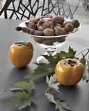 Khaki and walnuts on the table Stock Images