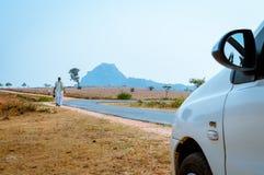 KHANDOLI, JHARKHAND, INDIEN - 25. JANUAR: Einsamen Leute, die in leere Straße an einem sonnigen Sommertag gehen Es ist ein wichti stockbild