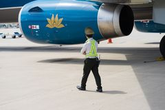 Khanh Hoa, Vietnam - 30 de julio de 2016: Personal de seguridad vietnamita que camina en la tierra de aviación con el aeroplano d Fotografía de archivo