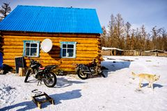 Khanh, Mongolia, Febrary, 24, 2018. Two motorcycles, sledge and dog in winter near wooden houses with blue roof stock photo