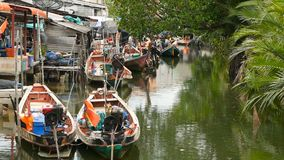Khanom, Thailand - September 21, 2018. Small boats in fisherman village on water of river in mangroves. Traditional Asia stock footage