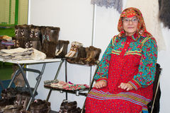 KHANTY-MANSIYSK, RUSSIA February 17, 2017. Woman in national costume of Finno-Ugric peoples in Khanty near national shoes. Royalty Free Stock Photo