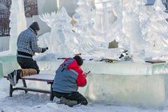 KHANTY-MANSIYSK, RUSSLAND - 2. DEZEMBER 2017: Angestellter im Marktplatz errichtet aus Stücken Eis, Eisskulptur, Affe heraus Stockfoto