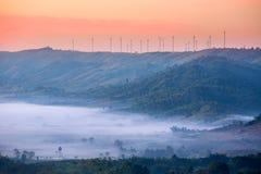 Khao Kho山脉边缘的风力农场与橙色天空和薄雾盖子的在作为背景的地面上 库存照片