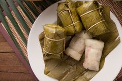 Khao tom mad Thai food style dessert, made from banana and glutinous rice, wrap with banana leaf on wooden table royalty free stock image