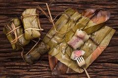 Khao Tom Mat - thailändsk efterrätt - klibbiga ris, bananen och svarta bönor som slås in i banan, spricker ut fotografering för bildbyråer