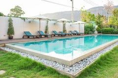 Swimming pool blue sunbed white umbrella in garden at prairie hills resort stock photography