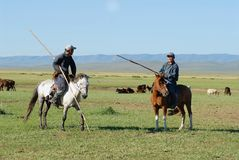 Two unidentified Mongolian men wearing traditional costumes riding on horse back talk in a steppe in Kharkhorin, Mongolia. royalty free stock photography