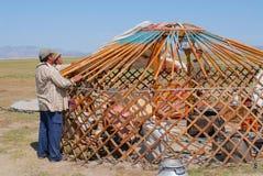 Mongolian men assemble yurt nomadic tent in steppe in Kharkhorin, Mongolia. KHARKHORIN, MONGOLIA - AUGUST 25, 2006: Unidentified Mongolian men assemble yurt stock photography