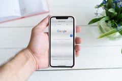 KHARKIV UKRAINA - April 10, 2019: Mannen rymmer Apple iPhone X med Google r Sökandesida arkivbilder