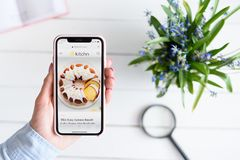 KHARKIV, UKRAINE - April 10, 2019: Apple iPhone X in female hand with thekitchn.com site on the screen royalty free stock image